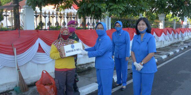 Foto Ketua Jalasenastri Lantamal IV daat membagikan drmbako kepada pekerja menyapu jalan